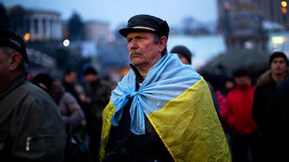 A man attends the funeral of anti-Yanukovych protester Bailuk Alexander, 40, killed in a recent clash with riot police in Kyiv's Independence Square, Ukraine, Friday, Feb. 28, 2014. (AP / Emilio Morenatti)