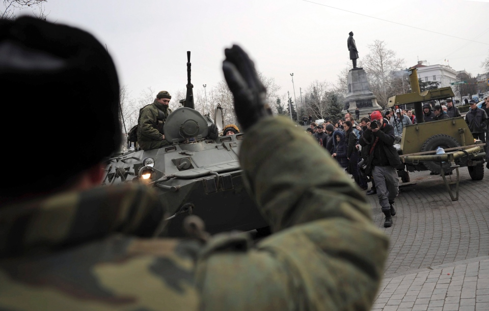 A Russian Army officer, back to camera, helps an armored personnel carrier drive on a street in Sevastopol, Ukraine's Black Sea Port that hosts a major Russian navy base Tuesday, Feb. 25, 2014. (AP / Andrew Lubimov)