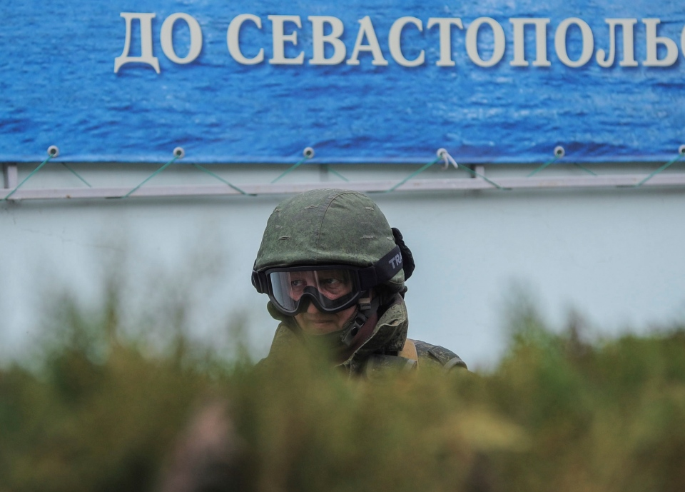 A gunman in unmarked uniform stands guard as troops take control the the Coast Guard offices in Balaklava, outskirts of Sevastopol, Ukraine on March 1, 2014. The word in the background reads 'To Sevastopol.' (AP Photo/Andrew Lubimov)