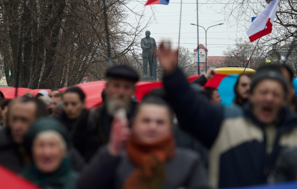 A statue of Soviet founder Vladimir Lenin in background as local residents carry giant Russian flags and shout slogans while rallying on the streets of Simferopol, Ukraine, on March 1, 2014. (AP / Ivan Sekretarev)