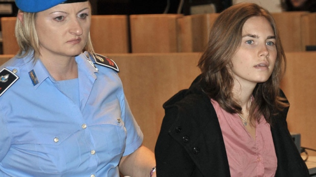 Amanda Knox, right, escorted by a penitentiary guard, arrives at the courthouse for the appeal trial in Perugia, Italy, Friday, Sept. 23, 2011. (AP Photo/Stefano Medici)