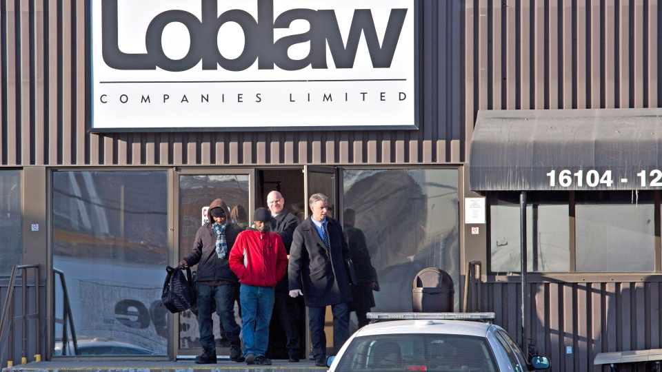 Police detectives walk out with witnesses as they investigate the scene where two people are dead and four people in hospital after a stabbing at a Loblaws warehouse in Edmonton, Alberta on Friday February 28, 2014. (Jason Franson / THE CANADIAN PRESS)
