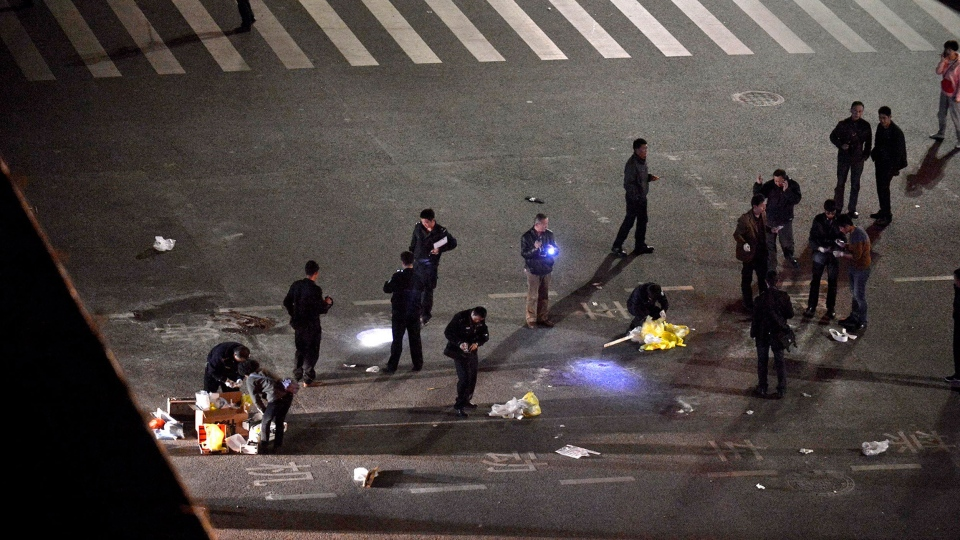 Police officers patrol outside a railway station after an attack by knife wielding men left some 27 dead in Kunming, in southwestern China's Yunnan province, Saturday March 1, 2014. (AP Photo)