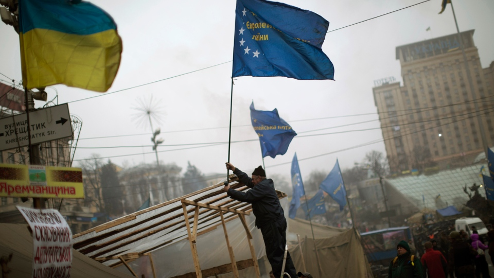 An anti-Yanukovych protester sets an European Union flag on top of a tent in Kyiv's Independence Square, the epicenter of the country's current unrest, Ukraine, Sunday, March 2, 2014. (AP / Emilio Morenatti)