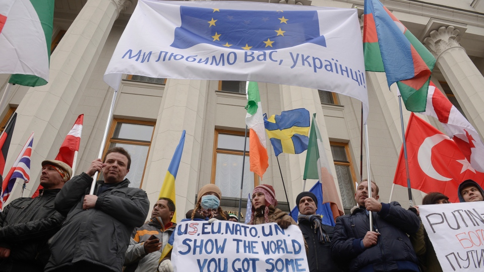 Foreign citizens rally to support Ukraine's territorial integrity in front of the parliament in Kyiv, Ukraine, Sunday, March 2, 2014. A poster reads :' Ukraine, we love you!' Ukraine's new prime minister urged Russian President Vladimir Putin to pull back his military Sunday in the conflict between the two countries, warning that 'we are on the brink of disaster.' (AP / Andrew Kravchenko)