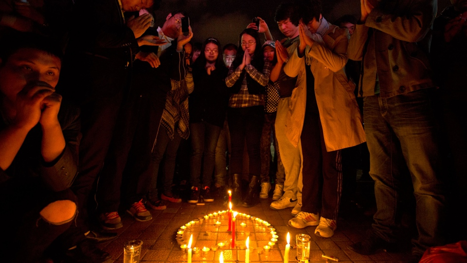 People light up candles and pray for the victims on a square outside the Kunming Railway Station where more than 10 assailants slashed scores of people with knives the night before in Kunming, in western China's Yunnan province, Sunday, March 2, 2014. (AP / Alexander F. Yuan)