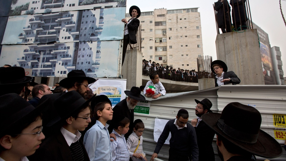 Ultra-Orthodox Jewish men participate in a rally against plans to force them to serve in the Israeli military, blocking roads and paralyzing the city of Jerusalem, Sunday, March 2, 2014. (AP / Sebastian Scheiner)