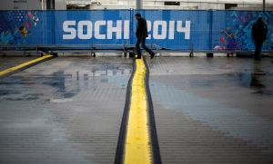 A man steps over one of several cable protectors next to the Iceberg Skating Palace at the 2014 Winter Olympics, Tuesday, Feb. 18, 2014, in Sochi, Russia. (AP/ David Goldman)