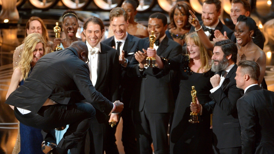 Director Steve McQueen, left, celebrates with the cast and crew of '12 Years a Slave' as they accept the award for best picture during the Oscars at the Dolby Theatre on Sunday, March 2, 2014. (John Shearer / Invision)