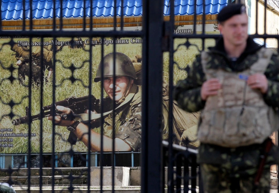 A Ukrainian soldier stands guard at the gate of a military base in the port of Kerch, Ukraine, Monday, March 3, 2014. (AP / Darko Vojinovic)
