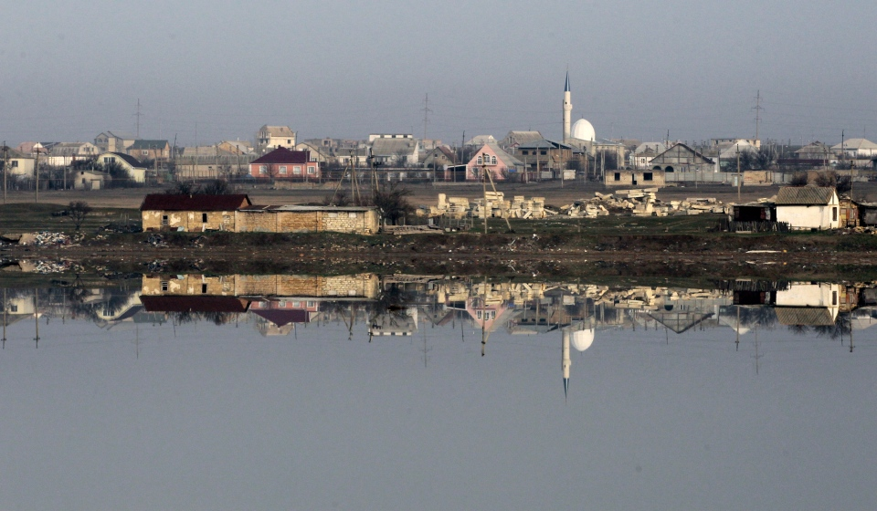 The town of Feodosiya is reflected in the small lake, in Crimea, Ukraine, Monday, March 3, 2014. (AP / Darko Vojinovic)