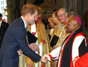 Prince Harry, left, shakes hands with South African Archbishop Desmond Tutu as he arrives at Westminster Abbey in London for a memorial service to honour former South African president Nelson Mandela, Monday March 3, 2014. (AP Photo / John Stillwell, pool)