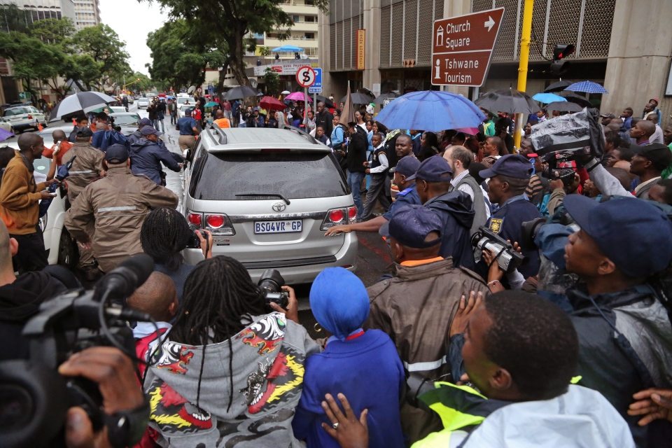 People run after the car that is transporting Oscar Pistorius from the high court after the first day of his trial in Pretoria, South Africa, Monday, March 3, 2014. (AP / Schalk van Zuydam)