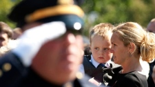 An officer salutes in front of Christine Russell, wife of fallen Toronto police Sgt. Ryan Russell, at a Police and Peace Officers' National Memorial DAy event in Ottawa, Ont. Sept. 25, 2011. ( THE CANADIAN PRESS/Fred Chartrand)
