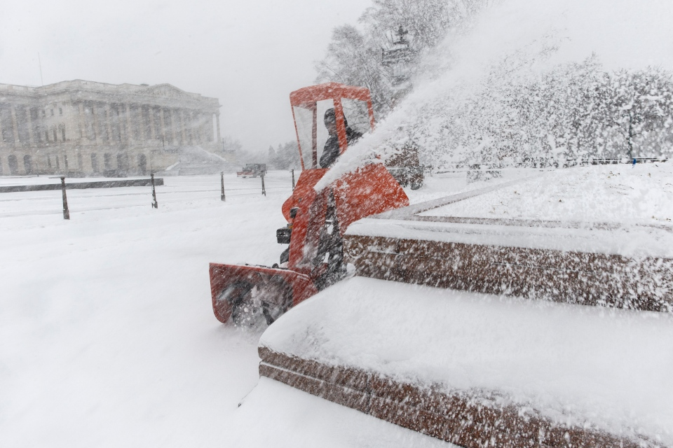 A Capitol Hill worker clears snow on Capitol Hill in Washington,Monday, March 3, 2014. (AP / J. Scott Applewhite)