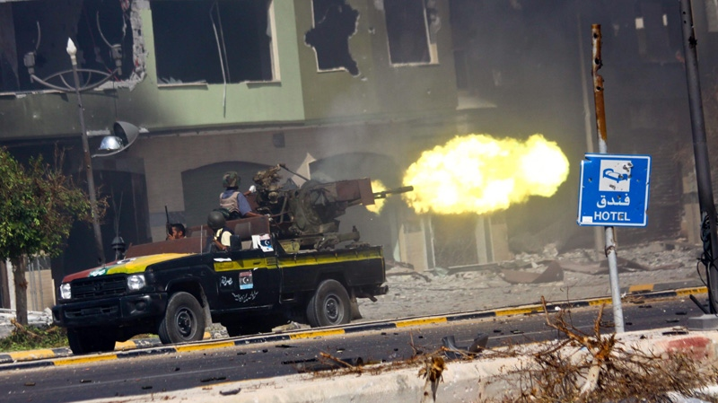 In this photo released by China's Xinhua News Agency, fighters of Libya's ruling National Transitional Council (NTC) fire at pro-Gadhafi forces during heavy battles at the entrance of Al-Etha'a street, about 7 kilometres from the heart of Sirte, Libya, Saturday, Sept. 24, 2011. (AP Photo/Xinhua, Amru Salahuddien)