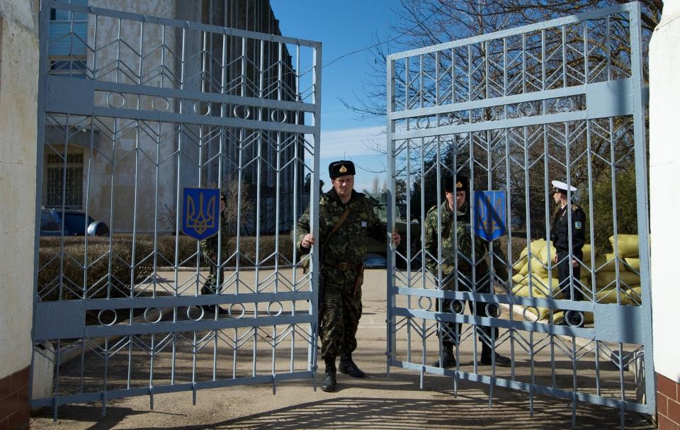 A Ukrainian soldier closes the naval base headquarter gate in the town of Novo-Ozerne, some 90 kilometres west of the Crimean capital Simferopol, Ukraine on March 3, 2014. (AP / Ivan Sekretarev)