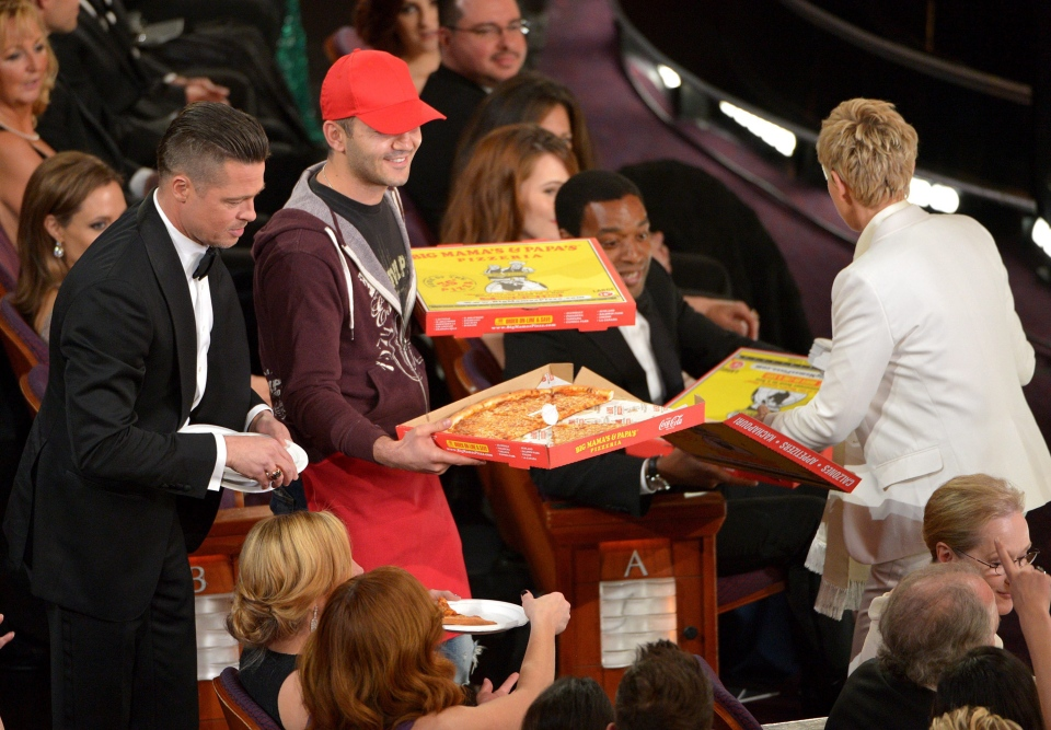 Brad Pitt, left, and Ellen DeGeneres, right, pass out pizza in the audience during the Oscars at the Dolby Theatre on Sunday, March 2, 2014, in Los Angeles. (John Shearer / Invision)