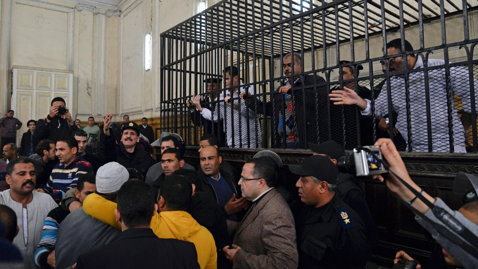 Caged policemen Awad Suliman, right, and Mahmoud Salah, fourth right, stand behind bars with security officials during the sentencing hearing of their retrial in the landmark case of the beating to death of 28-year-old Khaled Said, in the port city of Alexandria, Egypt, Monday, March 3, 2014. (AP / Heba Khamis)