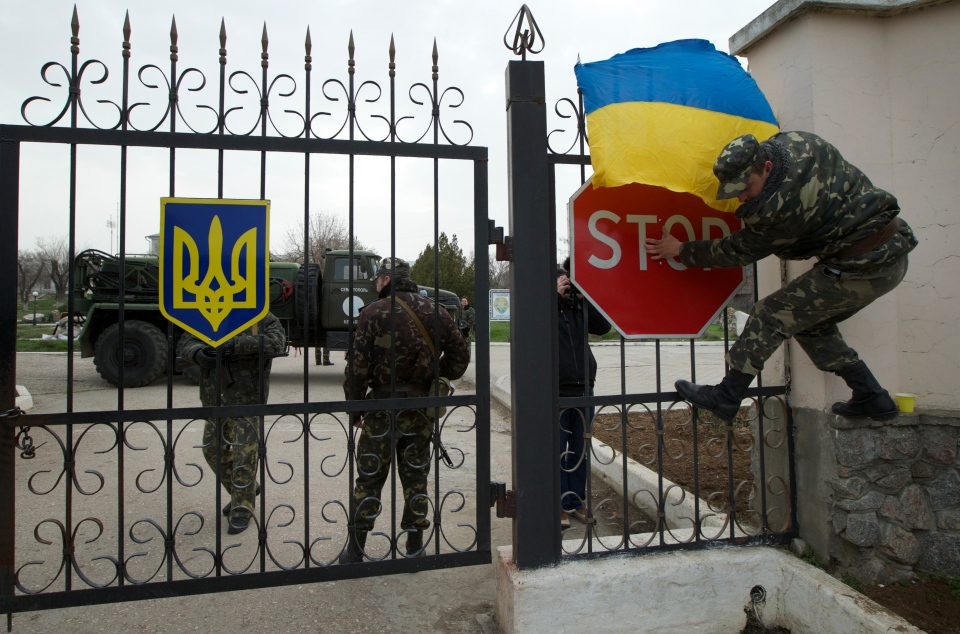 A Ukrainian airman puts the national flag over the gate as they guard what's left under their control at the Belbek air base, outside Sevastopol, Ukraine, on Tuesday, March 4, 2014. Russian troops, who had taken control over Belbek airbase, fired warning shots in the air as around 300 Ukrainian officers marched towards them to demand their jobs back. (AP / Ivan Sekretarev)