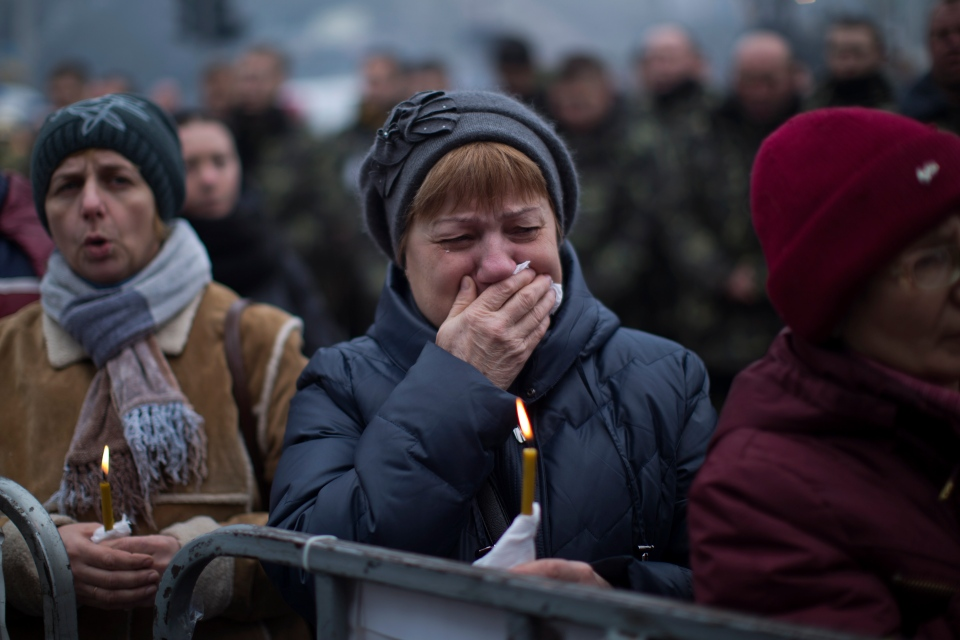 A woman cries during the funeral of Volodymyr Topiy, 59, who was found burned in the house of trade unions in Kyiv's Independence Square during recent clashes with police, Ukraine, Tuesday, March 4, 2014. (AP / Emilio Morenatti)