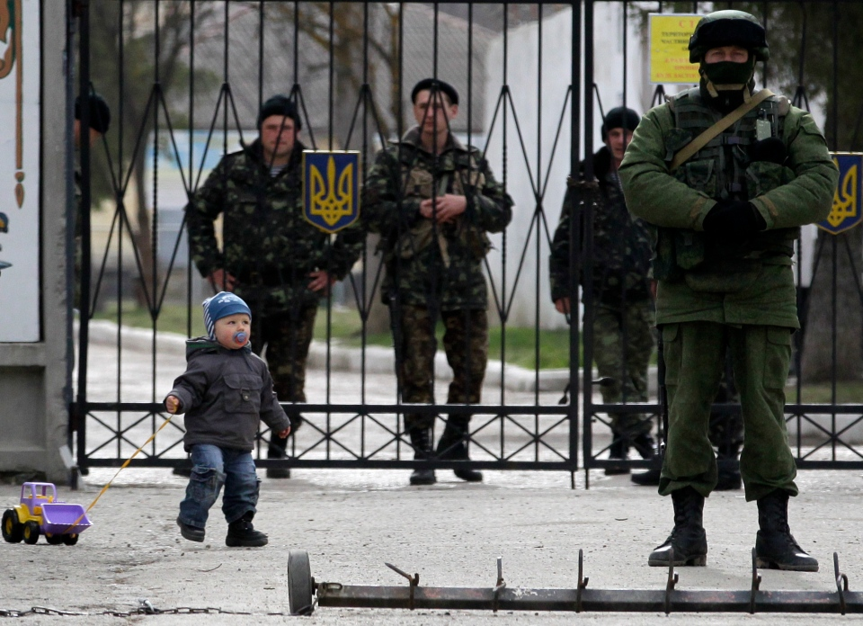 A child plays near a Russian soldier, right, while Ukrainian soldiers look on from behind gates as the Russian soldier guards the gate of an Ukrainian infantry base in Perevalne, Ukraine, Tuesday, March 4, 2014. (AP / Darko Vojinovic)