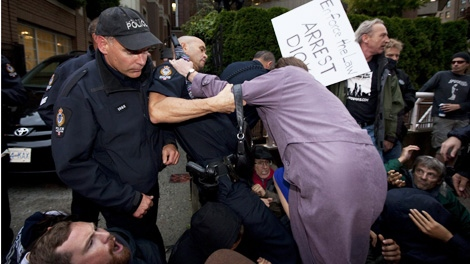 A police officer assists a lady to get past protesters opposed to former United States Vice-President Dick Cheney's visit to Canada rally outside where he is speaking in Vancouver Monday, Sept. 26, 2011. Cheney is in Vancouver to promote his new book and speak to members of the Bon Mot book club. (CP/Jonathan Hayward)