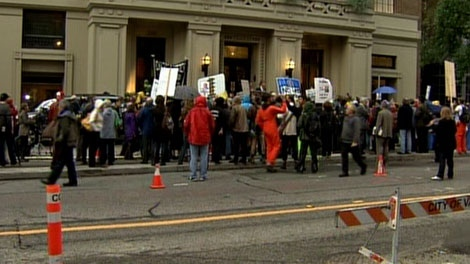 A large crowd of protesters gathered outside the Vancouver Club, where police escorted guests to an appearance by former U.S. vice-president Dick Cheney. Sept. 26, 2011. (CTV)