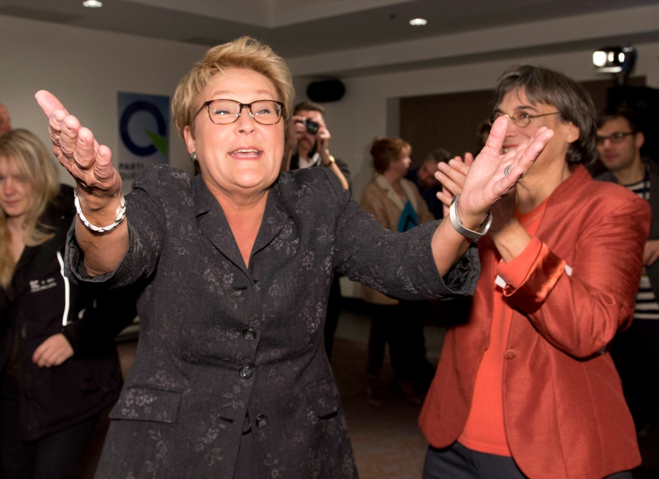 Quebec Premier and Parti Quebecois Leader Paulne Marois waves to applauding supporters as she enters a nomination meeting with Charlebourg candidate Dominique Payette, right, Tuesday, March 4, 2014 in Quebec City. THE CANADIAN PRESS/Jacques Boissinot