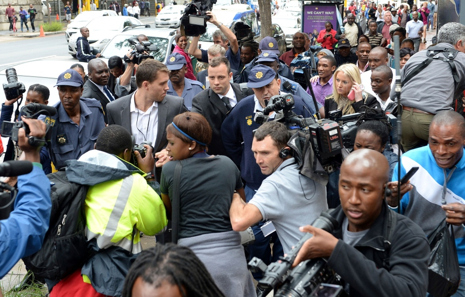 Oscar Pistorius, back centre, is mobbed by media as he is escorted by police outside court during a recess on the third day of his trial at the high court in Pretoria, South Africa, Wednesday, March 5, 2014. (AP / Antoine de Ras)