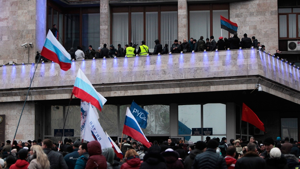 Demonstrators hold Russian flags during a rally in front of the regional administrative building after storming it in Donetsk, Ukraine, Wednesday, March 5, 2014. (AP / Sergei Chuzavkov)