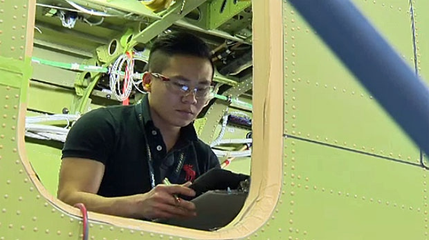A technician works on the interior of the plane at the Calgary plant.