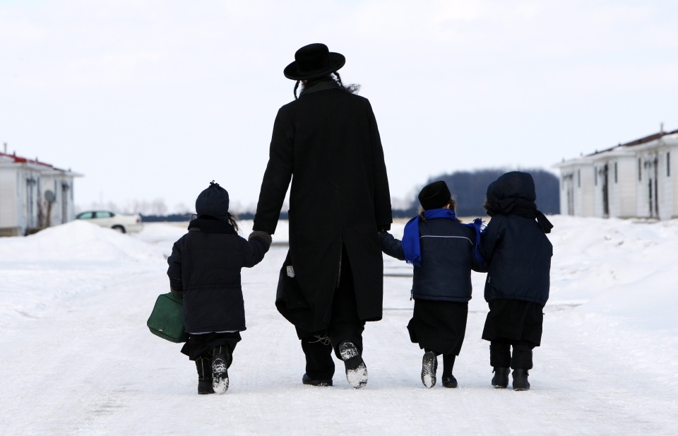 Members of the Lev Tahor ultra-orthodox Jewish sect walk down a street in Chatham, Ont., on Wednesday, March 5, 2014. (The Canadian Press/Dave Chidley)