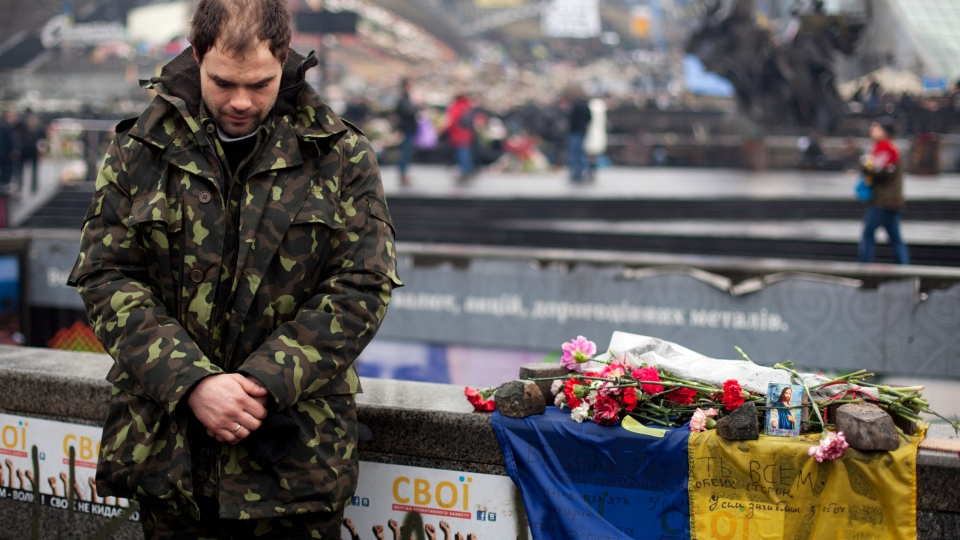 A Ukrainian self defense volunteer bows his head during a funeral ceremony for Andryi Pozniak, 25, who was also a self defense volunteer and who was shot and killed by an unknown assailant two days ago near Kyiv's Independence Square, Ukraine, Thursday, March 6, 2014. (AP / David Azia)