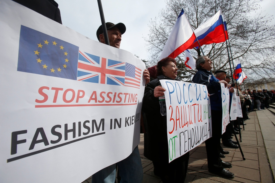 Pro-Russia demonstrators hold Russian and Crimean flags and posters as they rally in front of the local parliament building in Crimea's capital Simferopol, Ukraine, Thursday March 6, 2014. (AP / Sergei Grits)