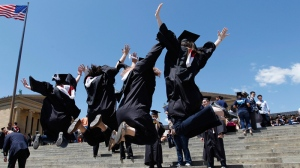 Graduating students from Temple University jump for a photo in Philadelphia. (AP / Alex Brandon)