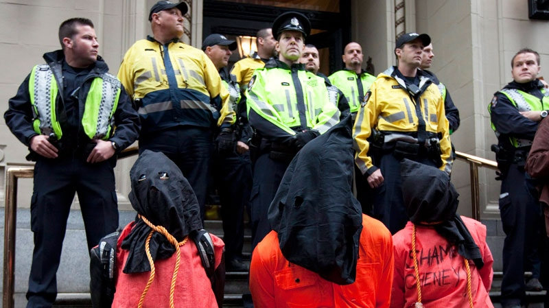Police look on as protesters opposed to former United States Vice-President Dick Cheney's visit to Canada rally outside where he is speaking in Vancouver Monday, Sept. 26, 2011. (Jonathan Hayward / THE CANADIAN PRESS)