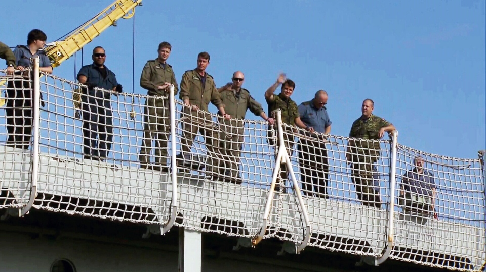 Sailors wave as HMCS Protecteur is towed into Pearl Harbor Thursday, March 6, 2014.
