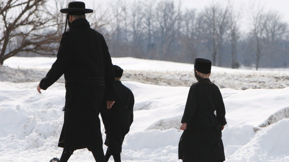 Members of the Lev Tahor ultra-orthodox Jewish sect walk down a street while an emergency motion in the child custody case is held at the courthouse in Chatham, Ont., Wednesday, March 5, 2014. (Dave Chidley / THE CANADIAN PRESS)