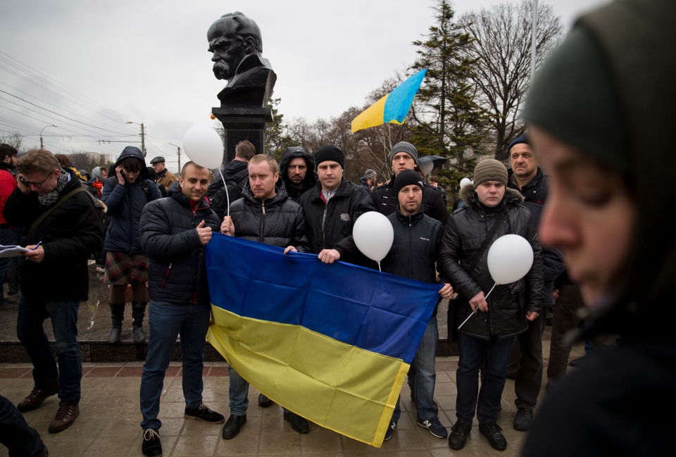 Ukrainians, back-dropped by a statue of Ukrainian poet and national symbol Taras Shevchenko, pose with the country's flag during a rally against the breakup of the country in Simferopol, Ukraine, Friday, March 7, 2014. (AP / Vadim Ghirda)