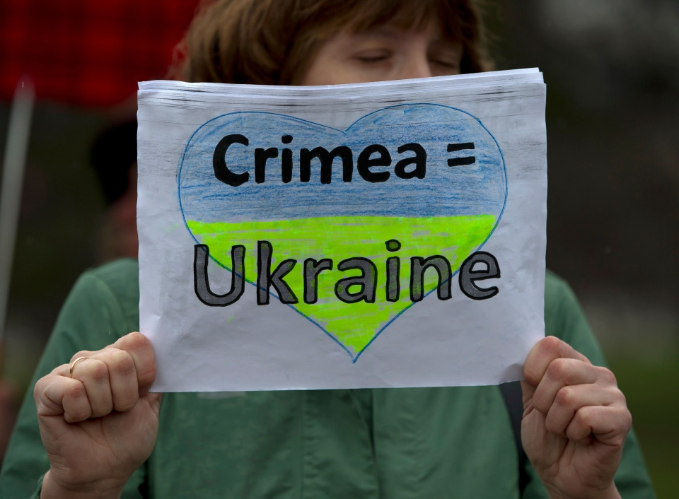 A woman holds a banner during a rally against the breakup of the country in Simferopol, Ukraine, Friday, March 7, 2014. (AP / Vadim Ghirda)