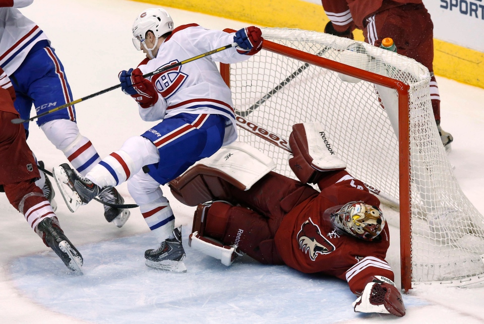 Montreal Canadiens' Brendan Gallagher, left, collides with Phoenix Coyotes' Mike Smith during the third period of an NHL hockey game Thursday, March 6, 2014, in Glendale, Ariz. The Coyotes defeated the Canadiens 5-2. (AP Photo/Ross D. Franklin)