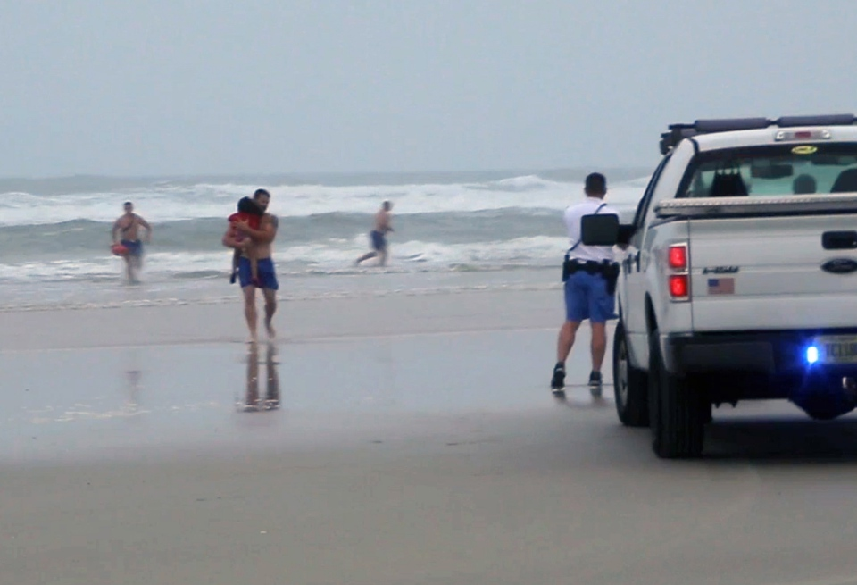 A lifeguard carries one of the three children rescued from a minivan that their mother, Ebony Wilkerson, drove into the Atlantic in Daytona Beach, Fla. in this March 4, 2014 image made from video. (AP / Simon Besner)