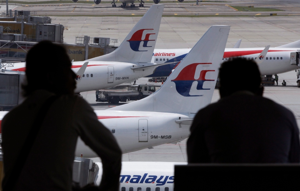 Passengers look at Malaysia Airlines' planes from a viewing gallery at Kuala Lumpur International Airport in Sepang, Malaysia, Wednesday, Aug. 21, 2013. (AP / Vincent Thian)