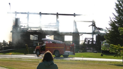 A bystander watches as fire crews battle a blaze at Aspen Links Country Club in Emerald Park on Wednesday.