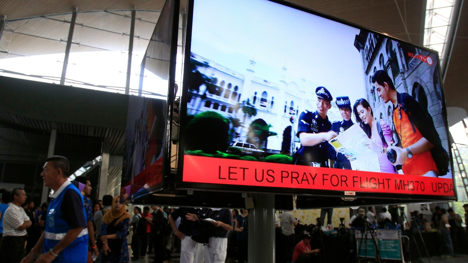 An information screen shows 'Let us pray for Flight MH370' at Kuala Lumpur International Airport in Sepang, outside Kuala Lumpur, Malaysia, Saturday, March 8, 2014. (AP / Lai Seng Sin)