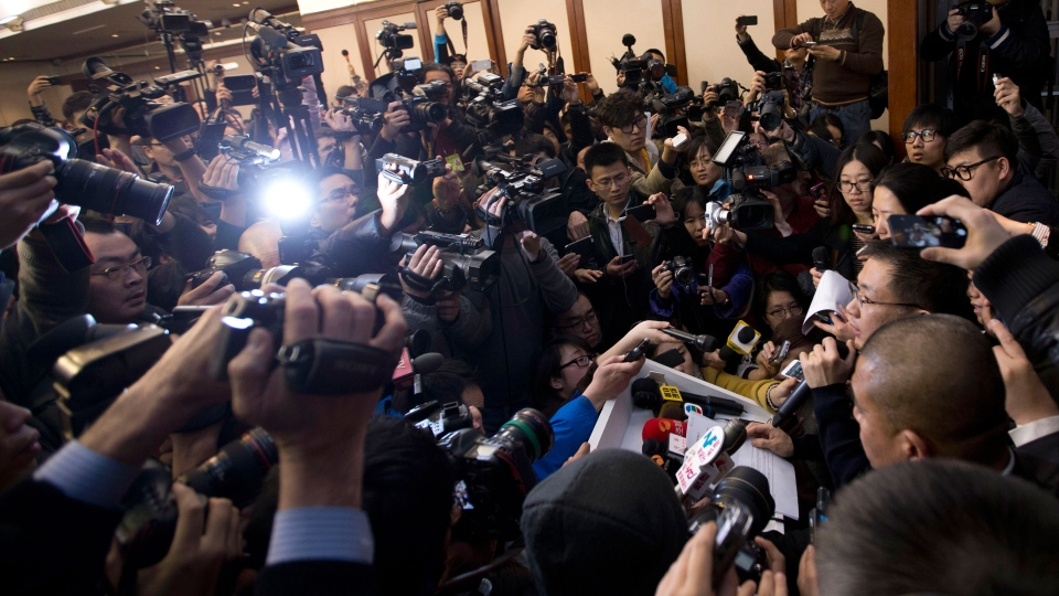 A spokesperson, right, from the Malaysia Airlines speaks to the media during a news conference at a hotel in Beijing Saturday, March 8, 2014. (AP / Andy Wong)