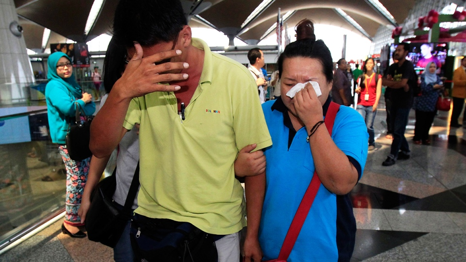 A woman wipes her tears after walking out of the reception centre and holding area for family and friend of passengers aboard a missing Malaysia Airlines plane, at Kuala Lumpur International Airport in Sepang, outside Kuala Lumpur, Malaysia, Saturday, March 8, 2014. (AP / Lai Seng Sin)