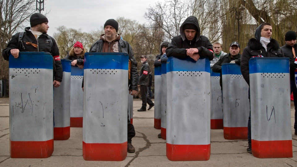 Volunteers of a self defense group lean on their shields while waiting to attend the swearing in of the first unit of a pro-Russian armed force, dubbed the 'military forces of the autonomous republic of Crimea' in Simferopol, Ukraine, Saturday, March 8, 2014. (AP / Vadim Ghirda)