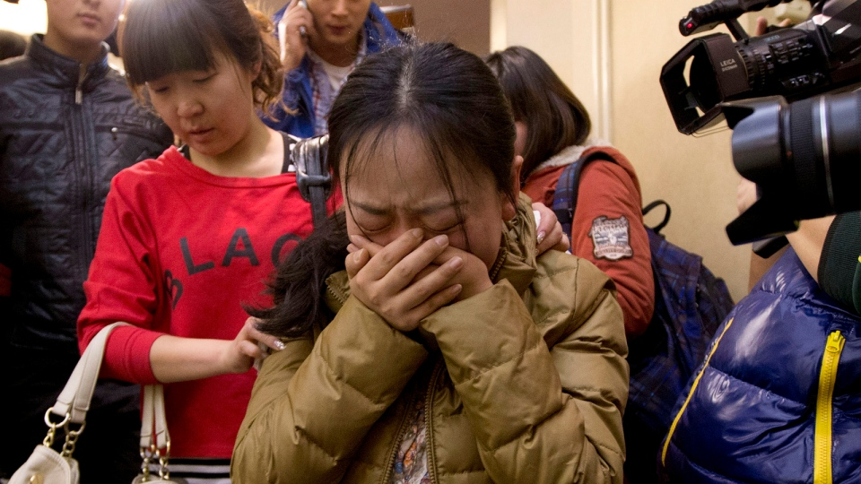 A Chinese relative of passengers aboard a missing Malaysia Airlines plane, centre, cries as she is escorted by a woman while leaving a hotel room for relatives or friends of passengers aboard the missing airplane, in Beijing, China, Sunday, March 9, 2014. (AP / Andy Wong)